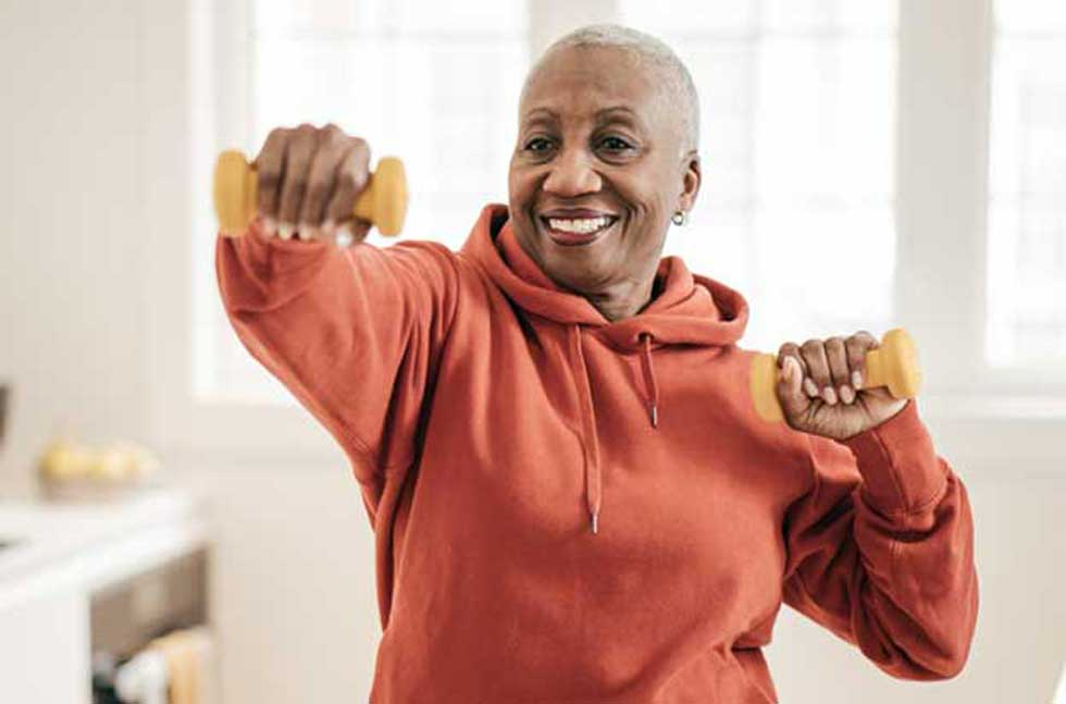 An older woman exercises and smiles after coordinate her care benefits with Population Health