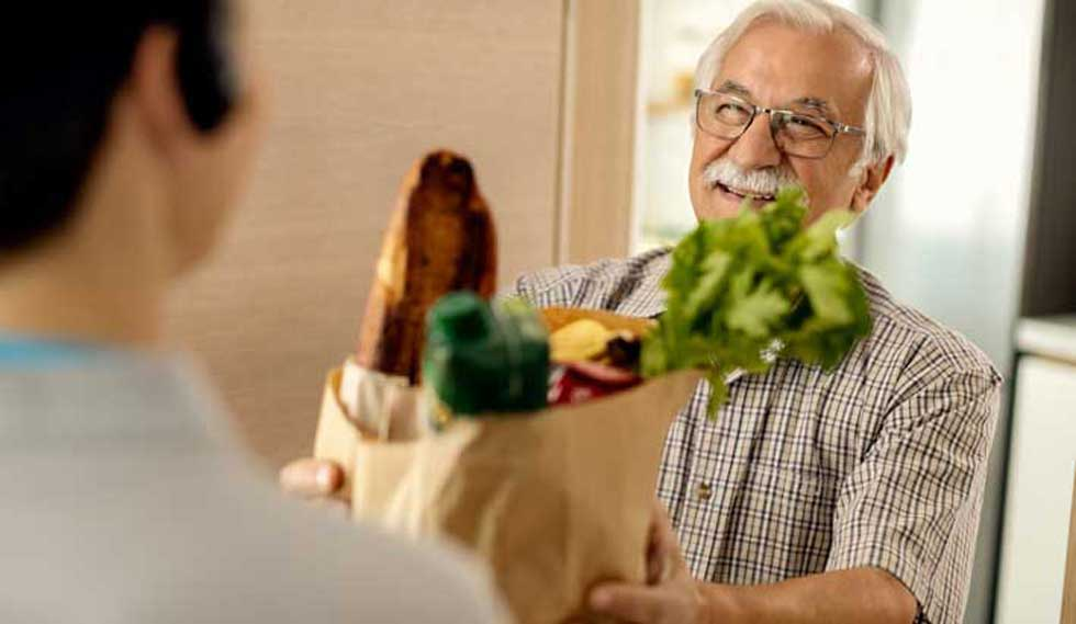 An older man accepts his meal delivery after working with Population Health