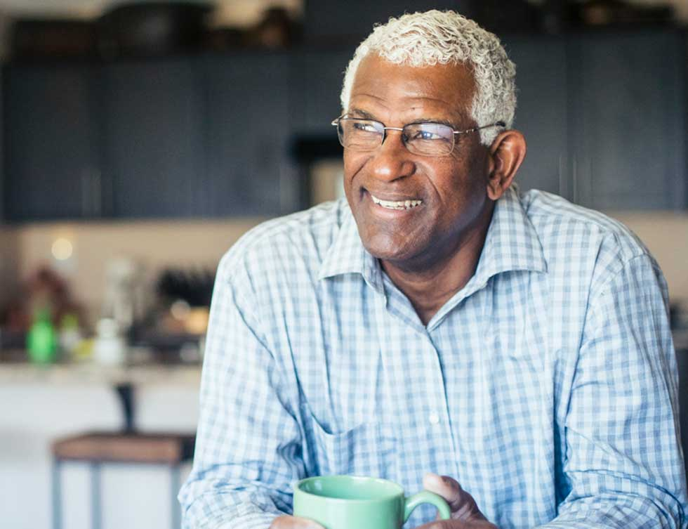 A man drinks his morning coffee and smiles after coordinating his care with Population Health